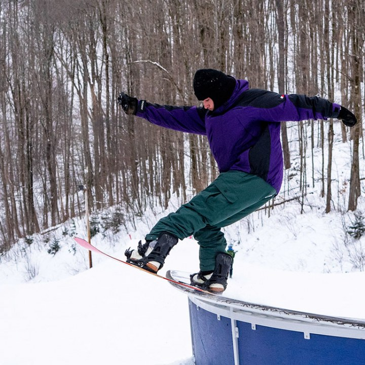 Snowboarder doing a trick on a box