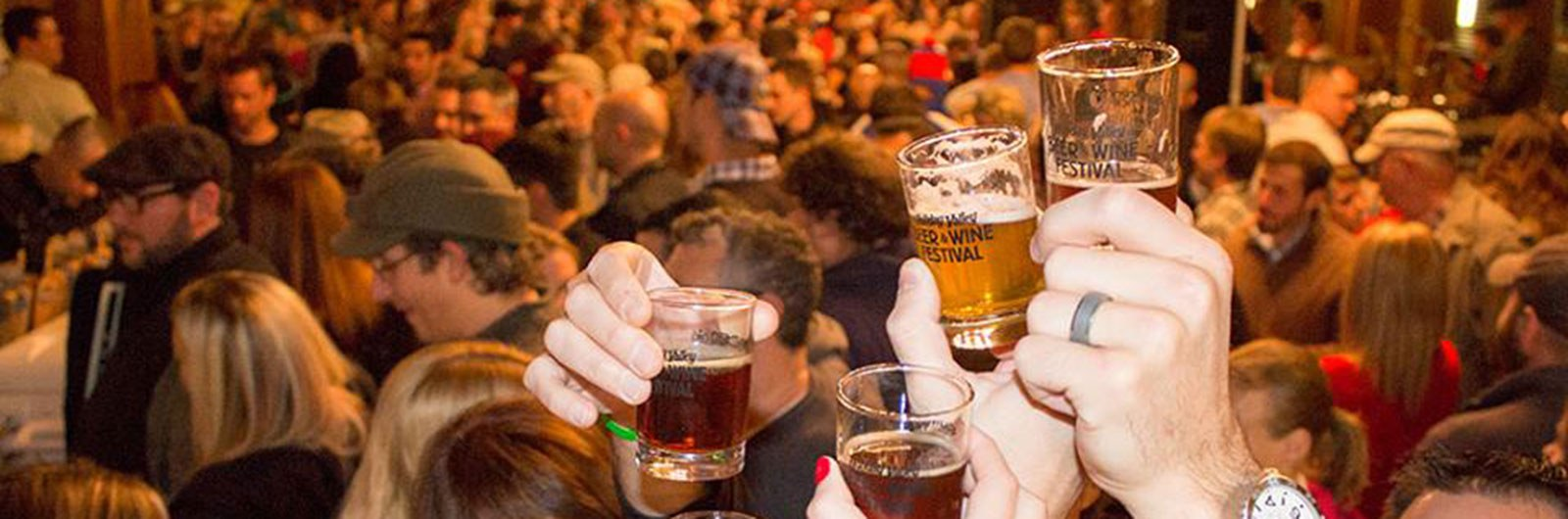 crowd raising glasses at beer and wine festival