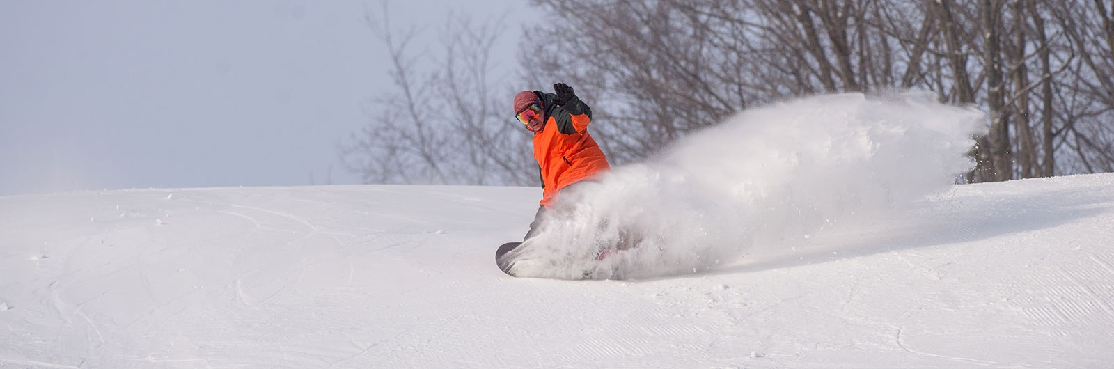 snowboarder spraying snow on The Wall slope