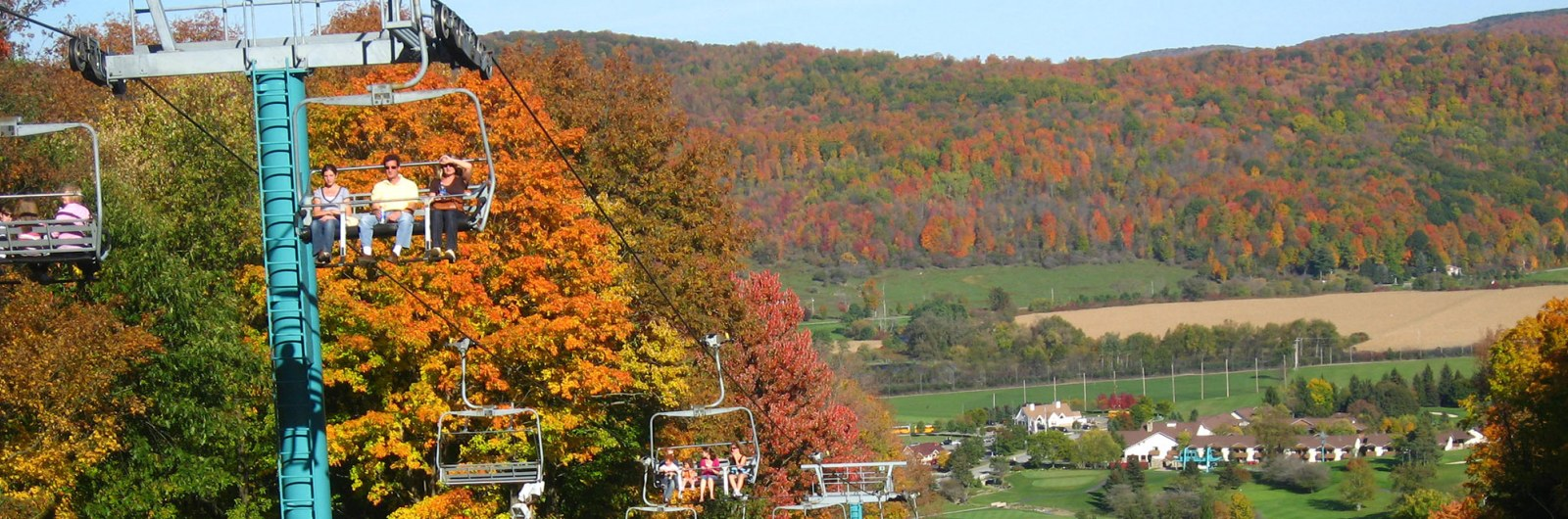 People riding the chairlift at Holiday Valley on a Fall day