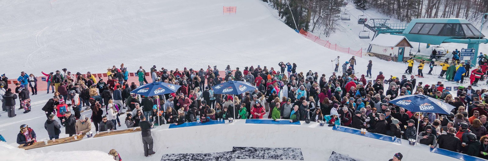 Spectators watching ski and snowboard event at base of mountain