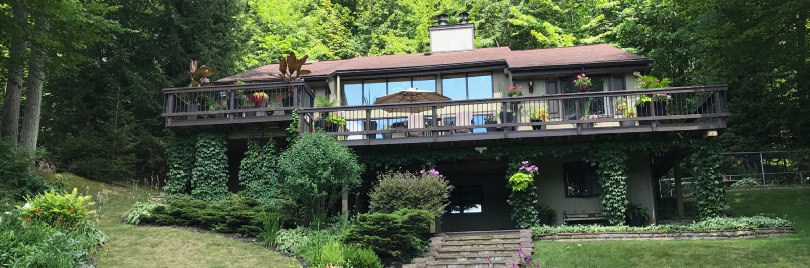 Mountain house with multiple decks surrounded by trees located near Holiday Valley ski resort in New York
