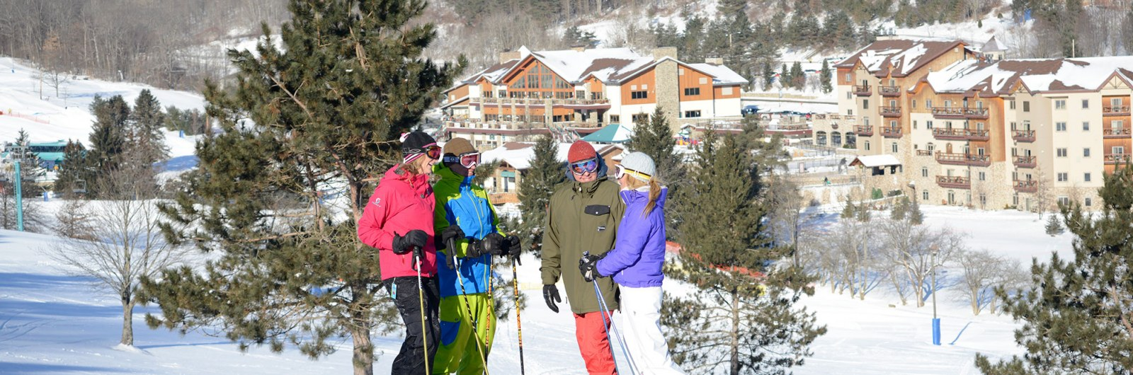 Two ski couples talking on the slope near the hotel by the ski mountain