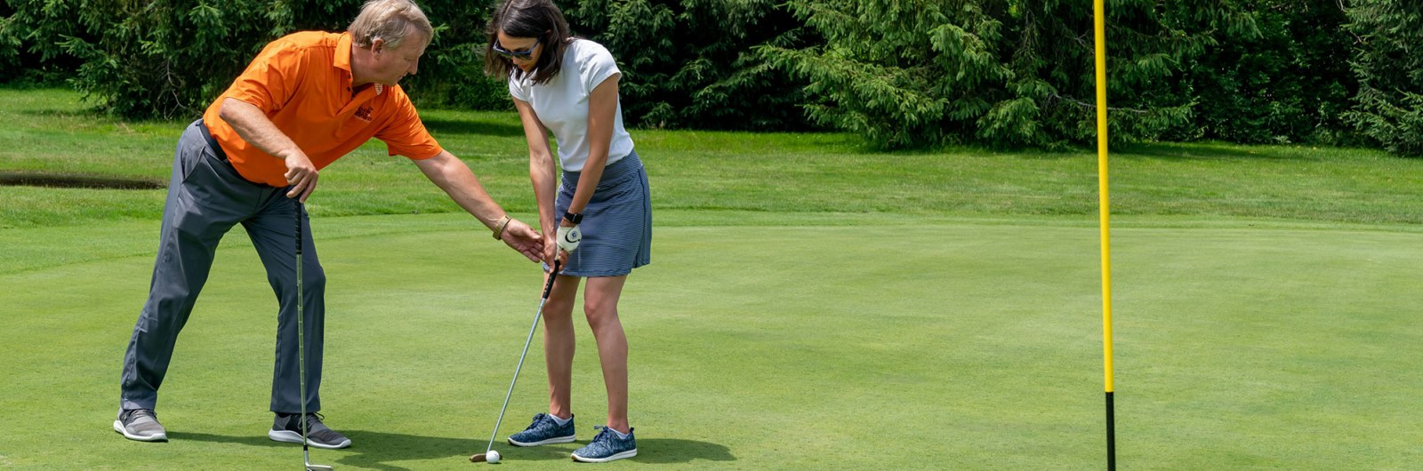 Golf instructor helping woman putt during golf lesson