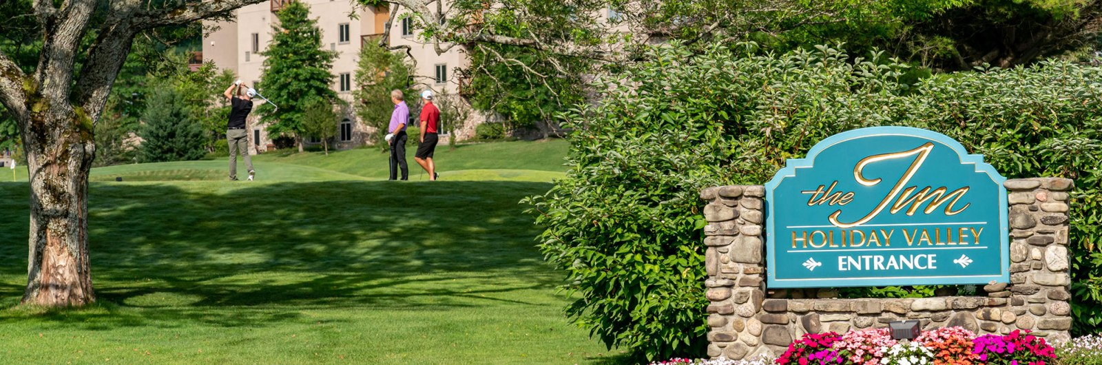Golfers teeing off on hole next to the Inn at Holiday Valley