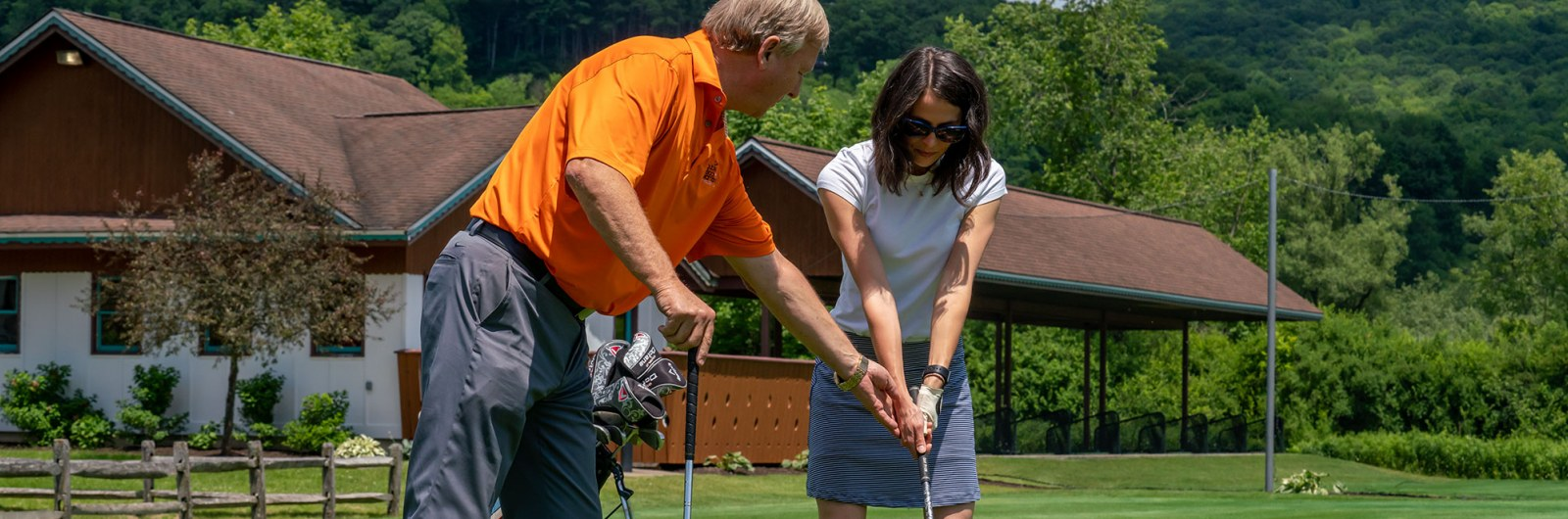 Woman taking golf lesson from instructor