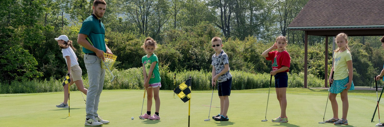 Group of children practicing putting with golf clinic instructor