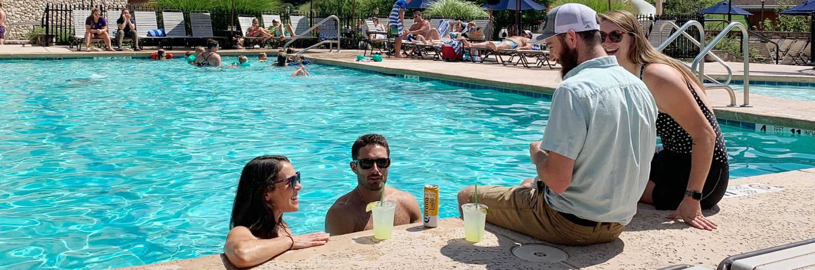 Two couples talking and enjoying drinks in the pool at Holiday Valley in New York