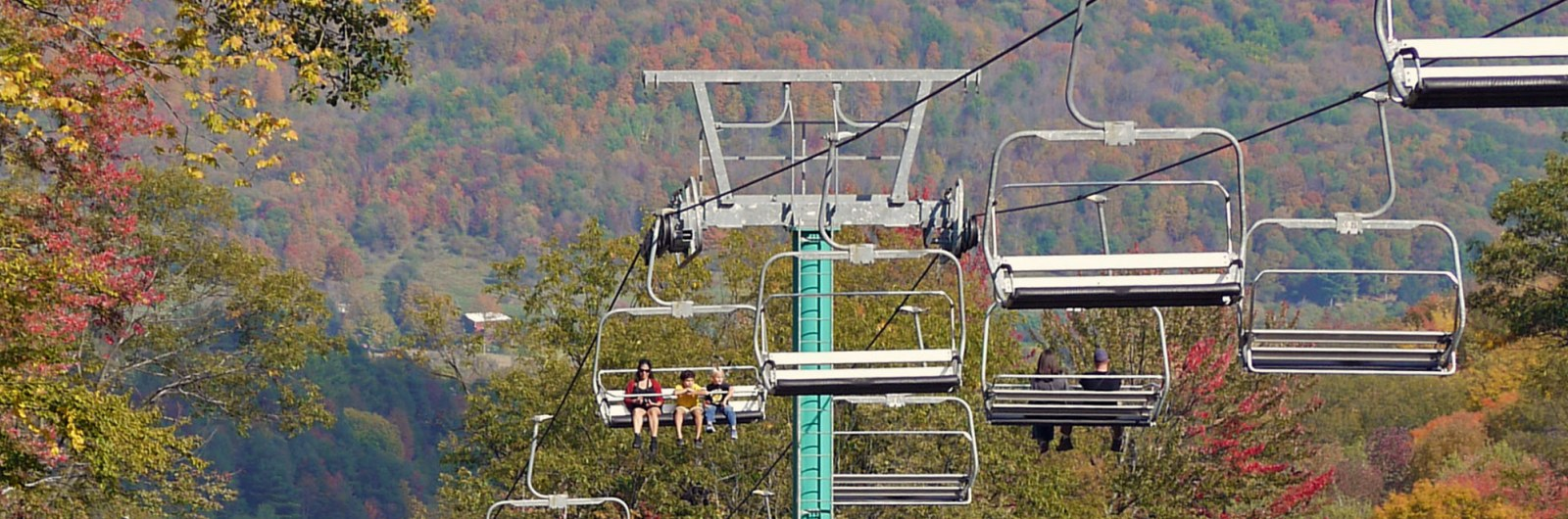 Mom with two children on chairlift ride during fall day