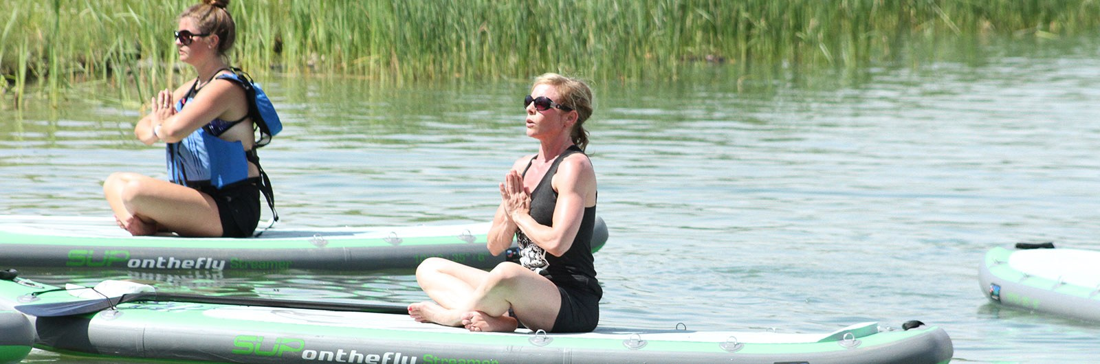 women practicing yoga on standup paddleboards