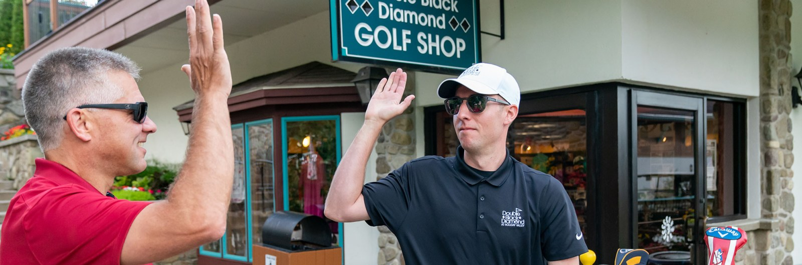 Two guys high five outside the golf shop at Holiday Valley