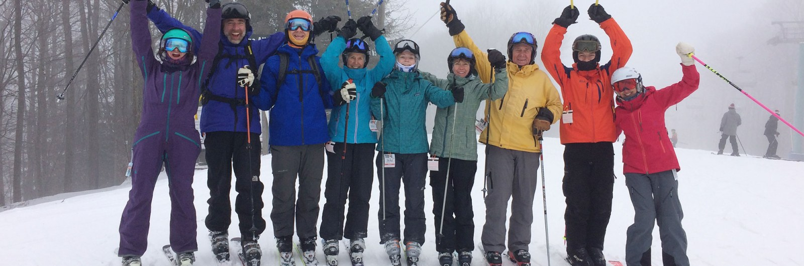Group of skiers cheering while posing for photo on the mountain