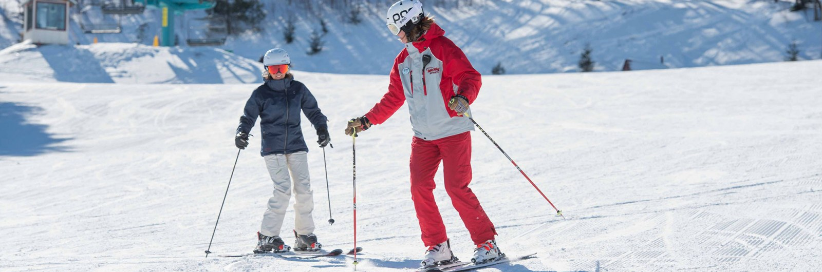Ski instructor slowly guiding skier down the hill during a lesson