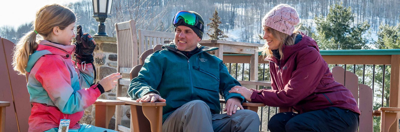 Parents and daughter sitting in adirondack chairs at ski resort on a winter day