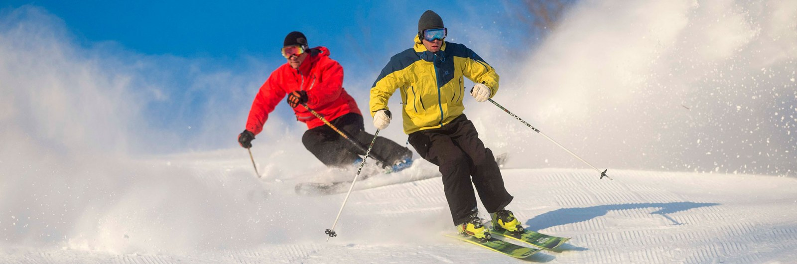 Two skiers carving and skiing fast down ski slope