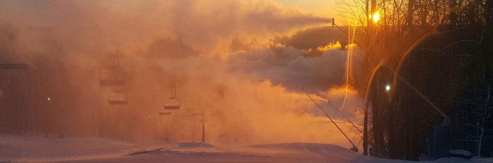 Snowmaking guns spraying snow over mountain slope during early morning sunrise