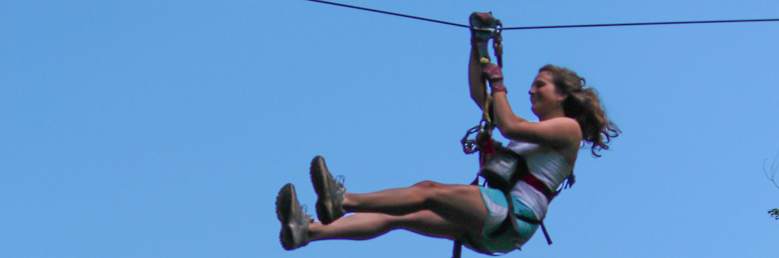 Woman zip lining at Sky High with blue sky background