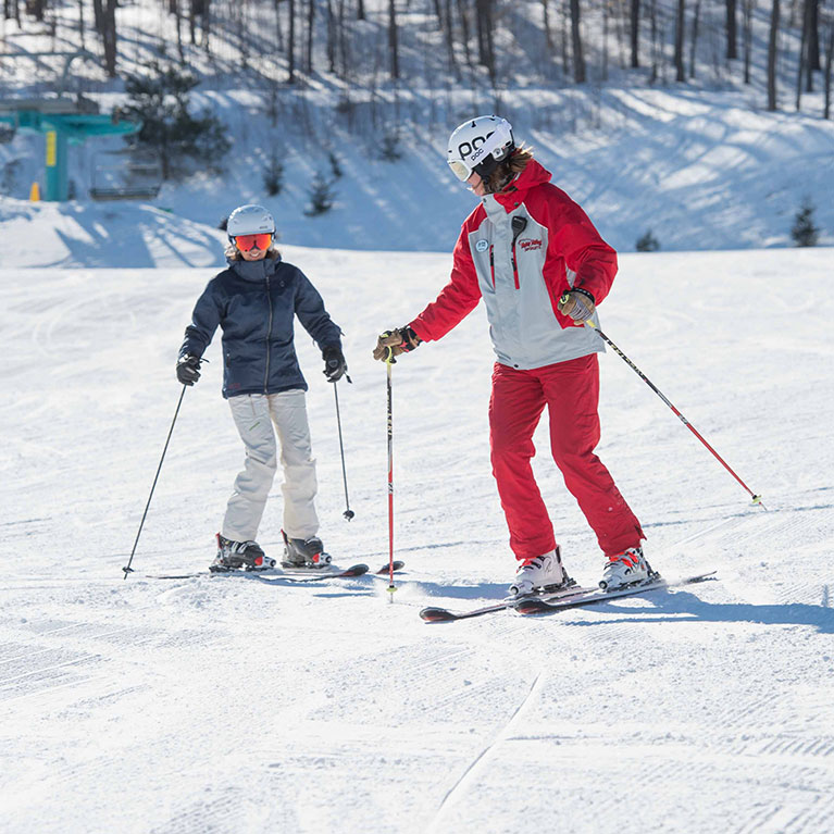 beginner skier and instructor