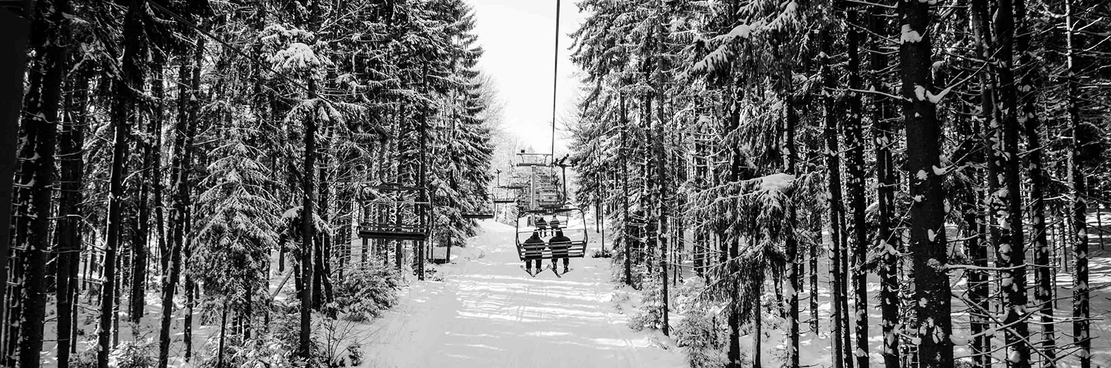 riding Tannenbaum chairlift between snowy trees
