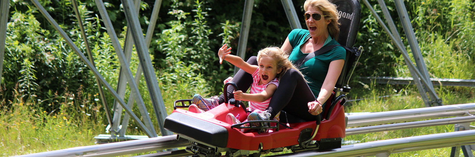 mother and daughter on mountain coaster in summer