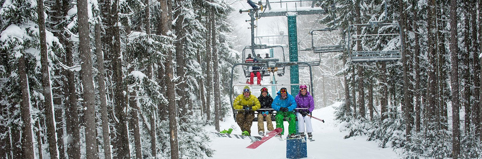 Four people riding up the Tannenabaum chair in winter