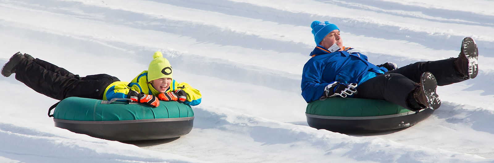 Boy and man snow tubing