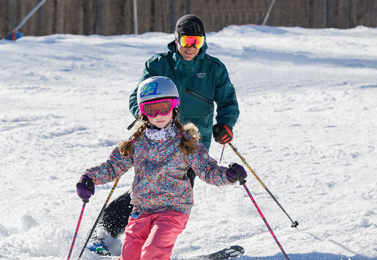 Dad and daughter skiing