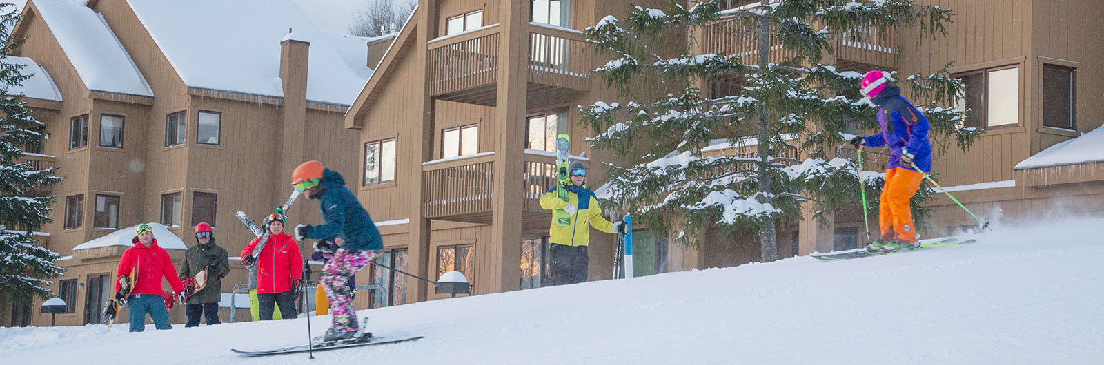 Skiers in front of SnowPine Village Condominiums