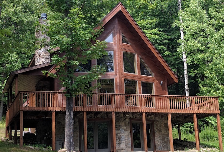 Mountain style home with large deck surrounded by trees near Holiday Valley in New York