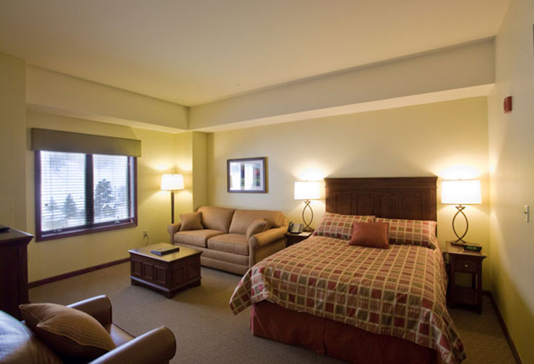 Deluxe hotel room with bed and couch at Holiday Valley
