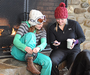 girls checking their phone by the fireplace
