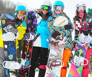 four snowboarder girls hanging out at the Rail Park