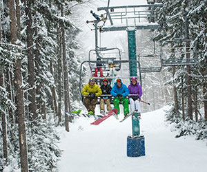 skiers riding Tannenbaum lift in snowstorm
