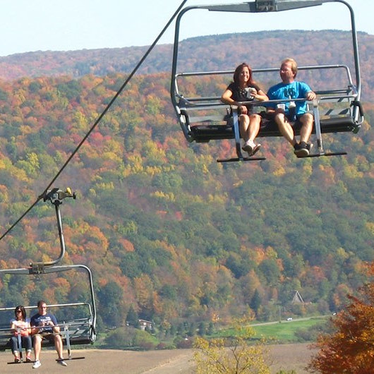 Guests riding ski chairlift during the fall