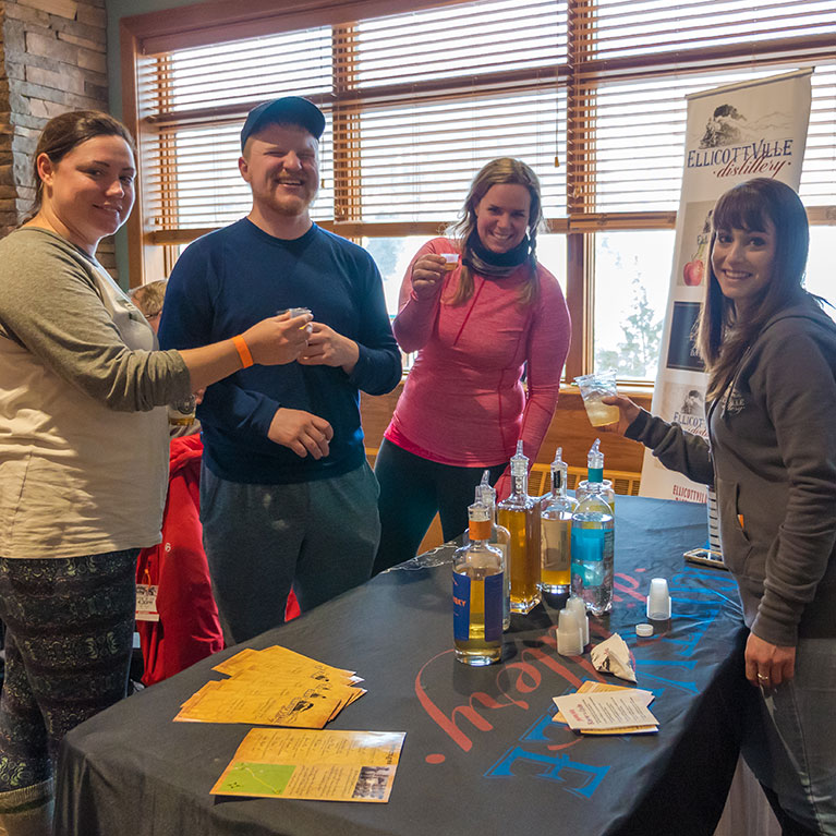 College kids cheers their drinks at Ellicottville Distillery tasting table