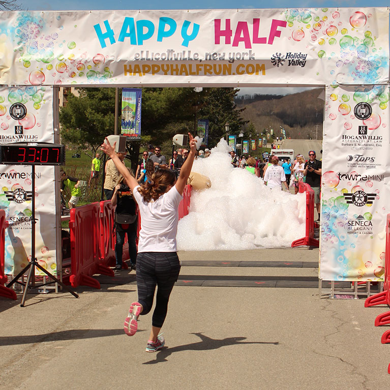 Runner crossing finish line with arms up after completing half marathon