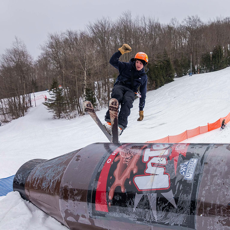 Skier jumping on barrel during rail jam event in the terrain park
