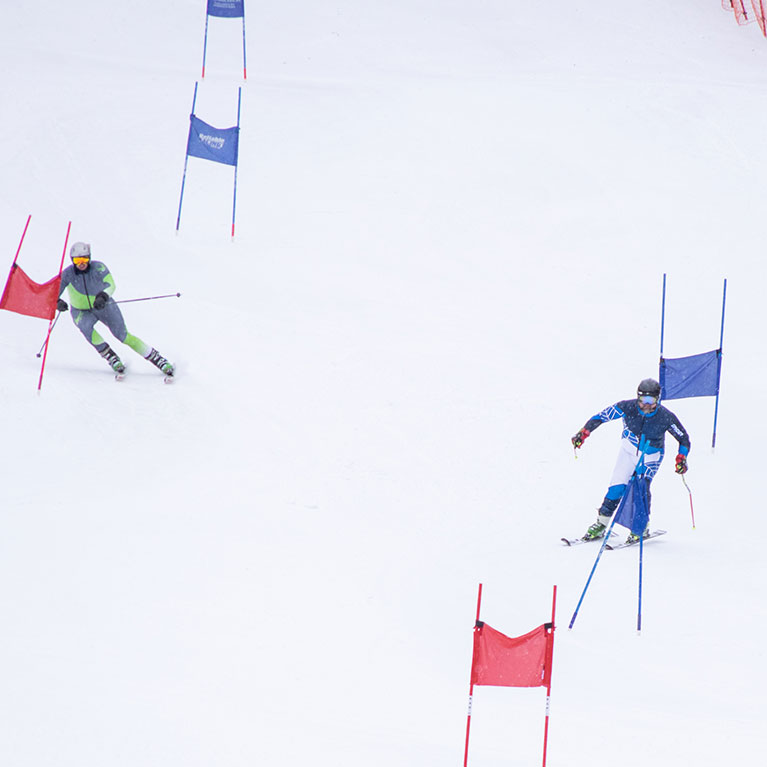 Racers skiing around slalom flags in downhill race