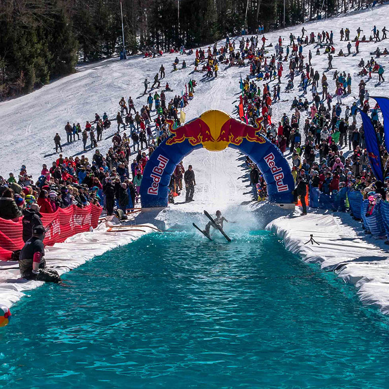 Crowd watching as skier tries to ski across water and falls in to fall in