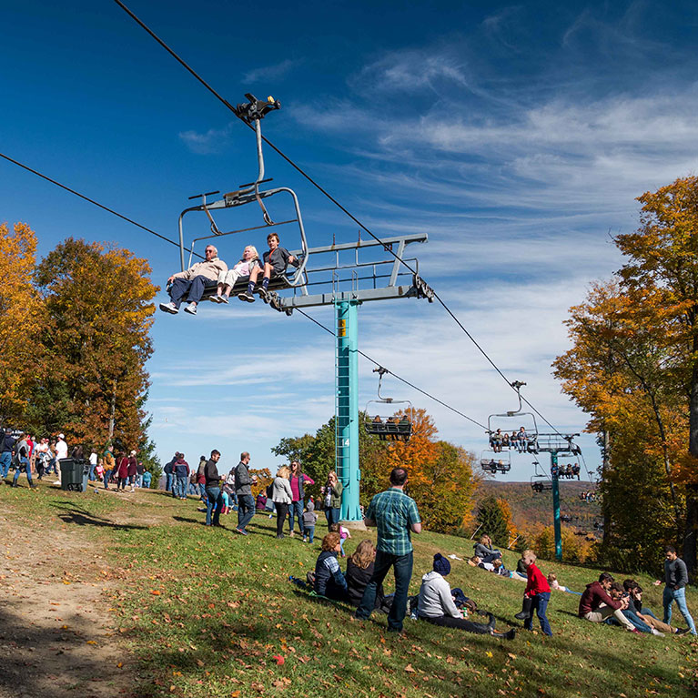 People enjoying fall chairlift rides and relaxing in the grass