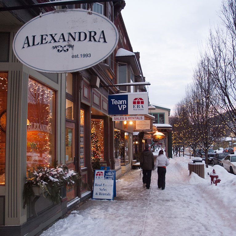 Couple walking past shops on main street in Ellicottville Village during winter