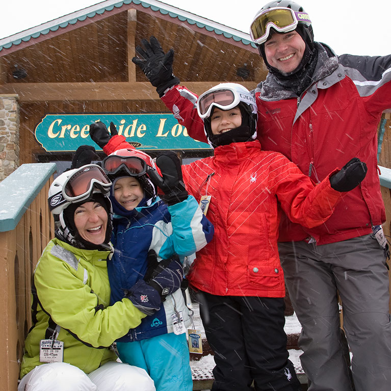 Parents and two kids in ski gear posing for photo outside of ski lodge