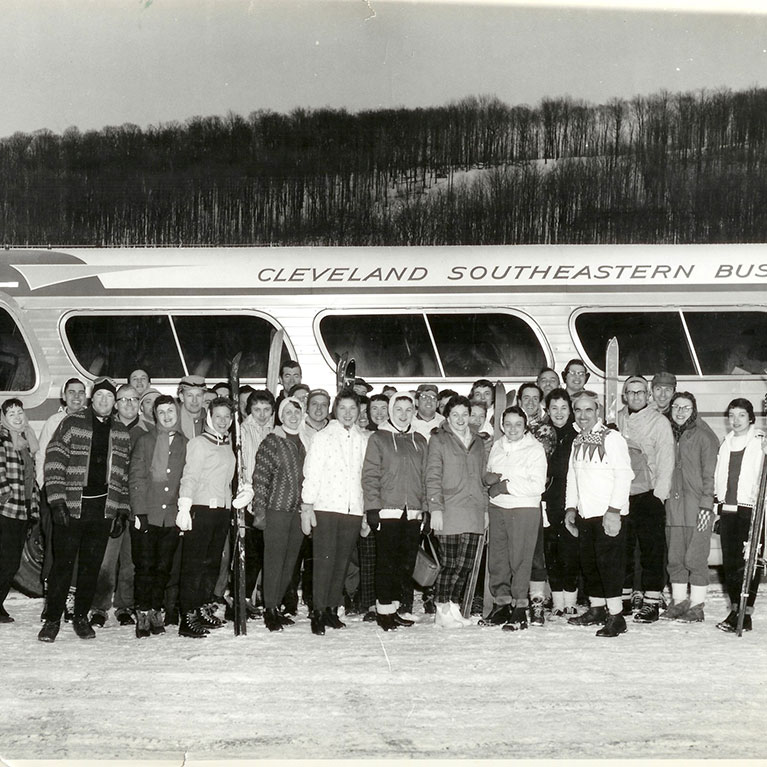 Historical photo of ski group posing for photo in front of tour bus
