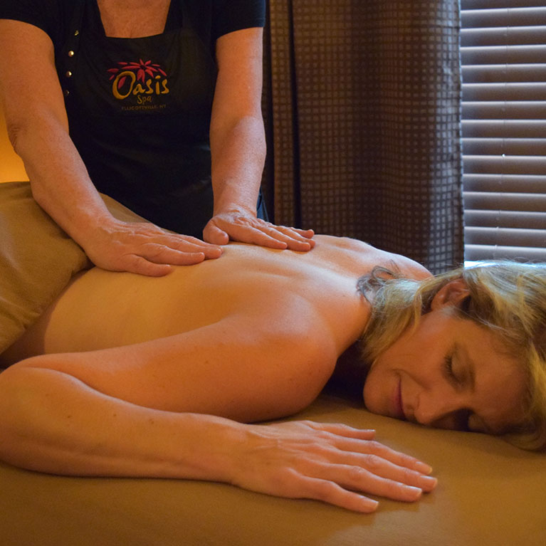 Woman getting back massage on massage table at spa