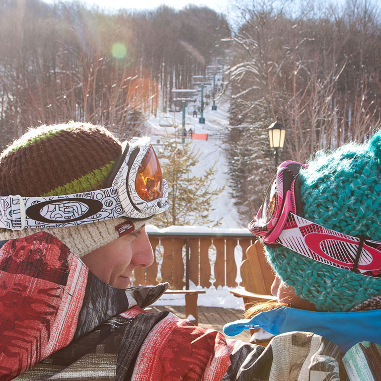 Ski couple looking at each other while sitting with view of mountain chairlift