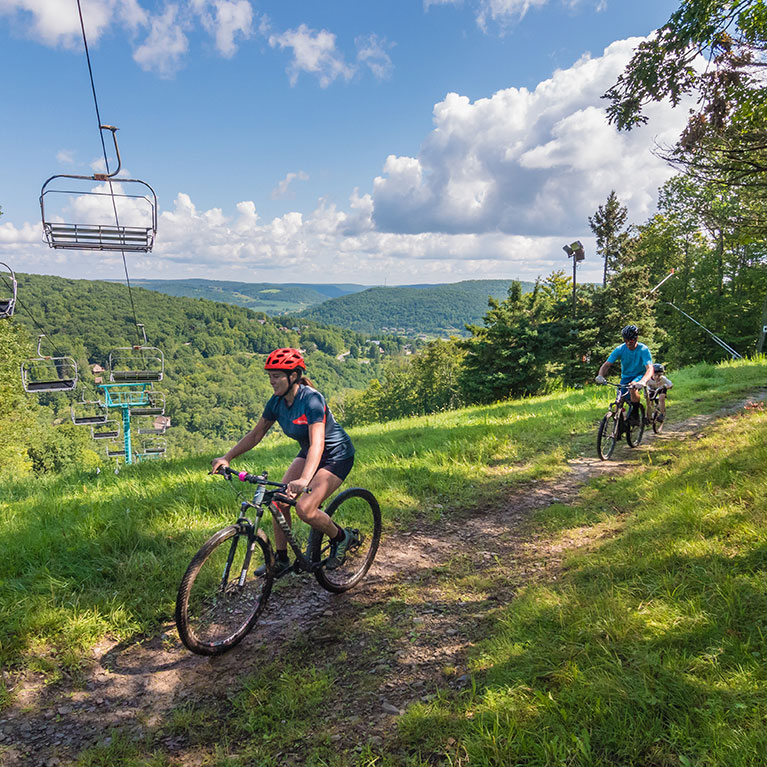 Family riding mountain bikes on path that crosses under chair lift