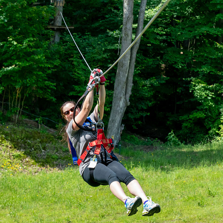 Woman in harness riding zipline