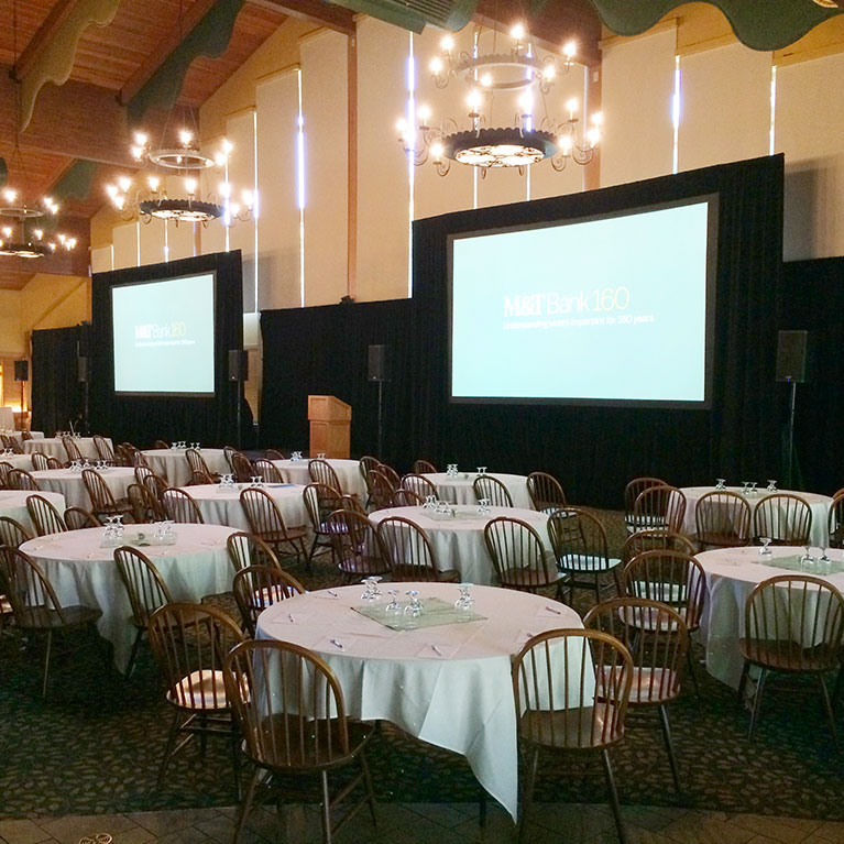 Ballroom set up with banquet tables and projector screens.