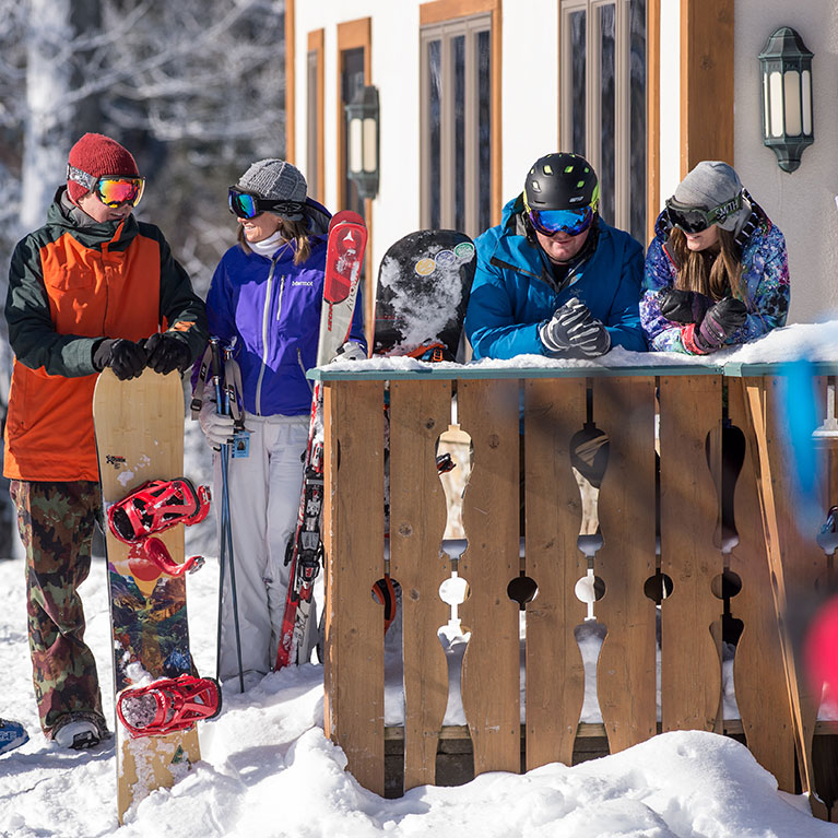 Two ski and snowboard couples talking outside the ski lodge