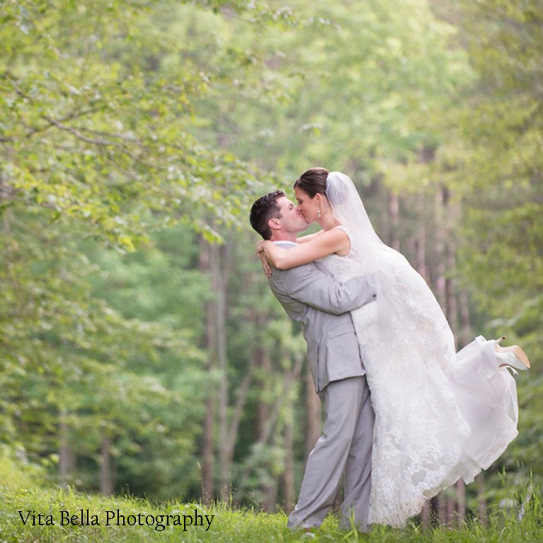 Groom kissing bride outside in the woods next to wedding venue in NY